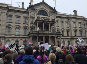 Listening to Edith Savage-Jennings speak on the steps of the Statehouse. Source: Emma Piasick
